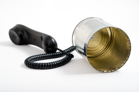 using voice: telephone and tin can on a white background. technological leap.