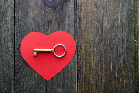 golden key: red paper heart and golden key on a wooden surface