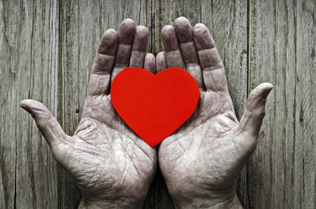 longing: paper heart in the hands of an elderly. Wooden background Stock Photo