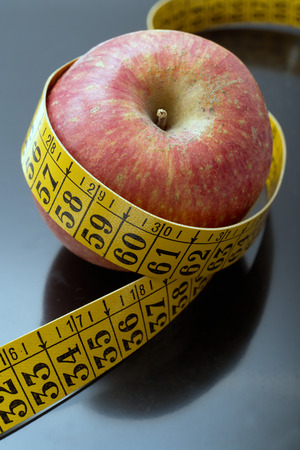 cordon tape: apple with tape measure. dark background Stock Photo