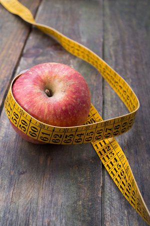cordon tape: apple with tape measure. wooden background