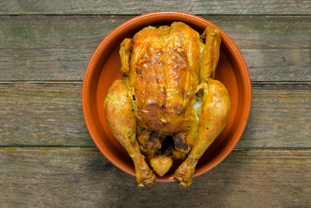 clay pot: grilled chicken served in a clay pot and on a rough wooden table