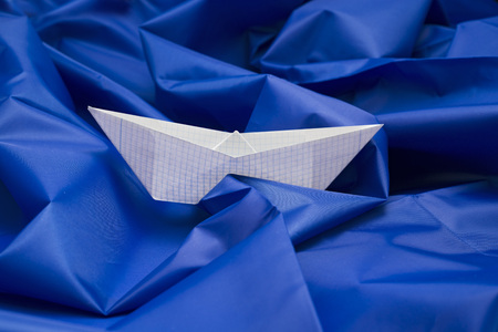 paper boat: Paper boat on blue fabric Stock Photo