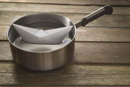 paper boat: Paper boat sailing in a saucepan. Wooden background Stock Photo