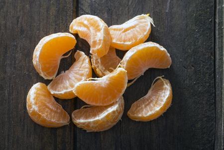 mandarin orange: mandarin orange sections on a wooden table