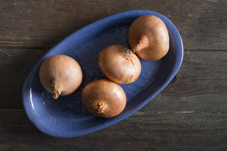 pealing: Onions in a blue tray on a rustic wooden table