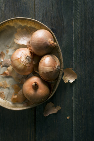 pealing: Onions in a cardboard tray on a rustic wooden table Stock Photo