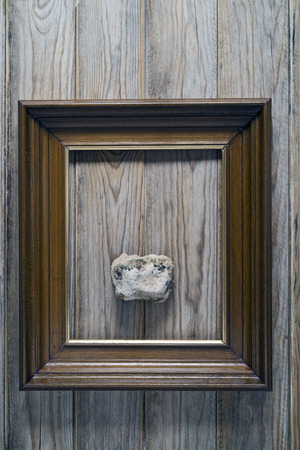 foolish: stone in a frame on a wooden wall