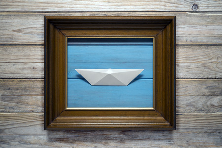 naivete: Frame with paper boat on wood background