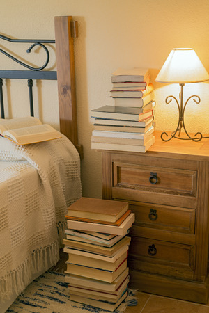 nightstand: books stacked on a nightstand next to a bed