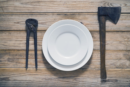 inappropriate: Ax and tongs as tableware Stock Photo