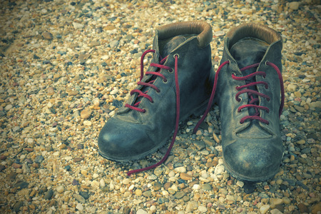 outdoor pursuit: old boots on a gravel floor. Vintage edition
