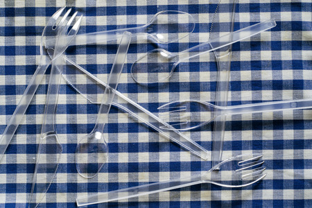 throwaway: plastic cutlery on a checkered tablecloth