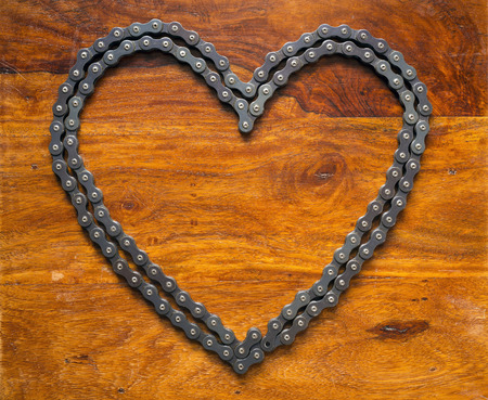 link work: Heart made of chain on wooden table Stock Photo