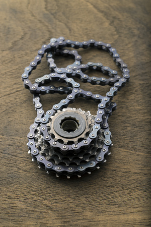 bicycle gear: bicycle gear cogwheel and chain over wooden surface