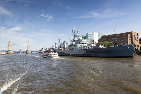 hms: HMS Belfast on the River Thames in London, with the Tower Bridge in the background. Editorial