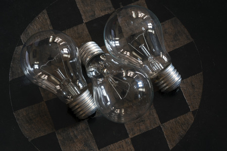 penumbra: three light bulbs turned off on a checkered surface Stock Photo