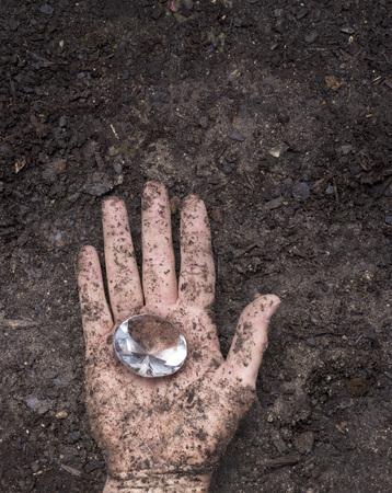diamond shaped: muddy dirty hand holding a glass diamond shaped