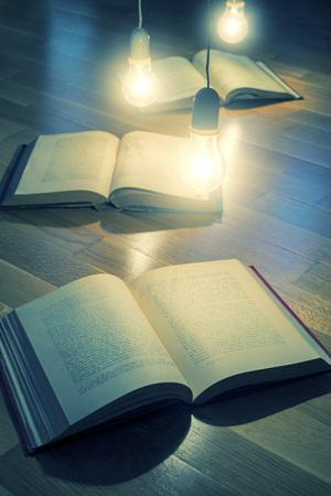 illuminating: electric bulb illuminating a book