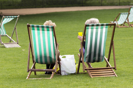 st jamess: St. Jamess Park, London: Two women sitting in deck chairs talking after a morning of shopping