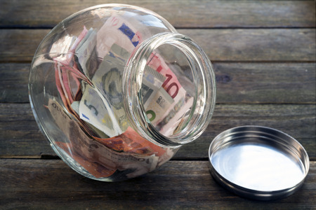 billets euro: Euro notes in a glass jar on a wooden table