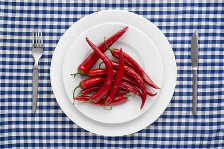 peppery: Red chilli peppers on a checkered tablecloth Stock Photo