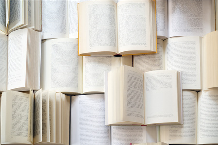 unreadable: Many open books piled up. unreadable text