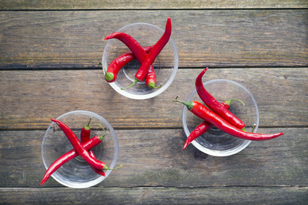 peppery: three glass bowls containing red chillies Stock Photo