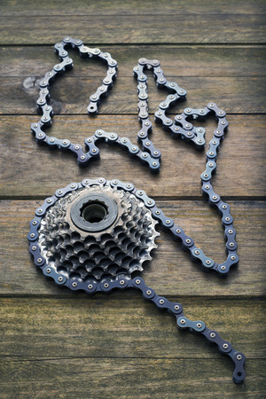 liaison: bicycle gear cogwheel and chain over wooden surface