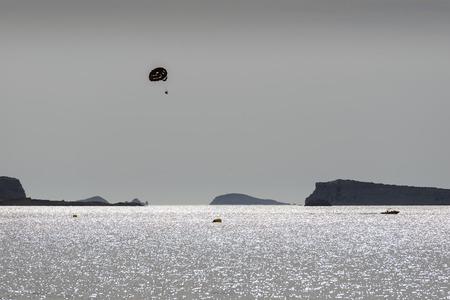 kiting: Ibiza. Parasailing - summer kiting activity, person is towed behind a boat