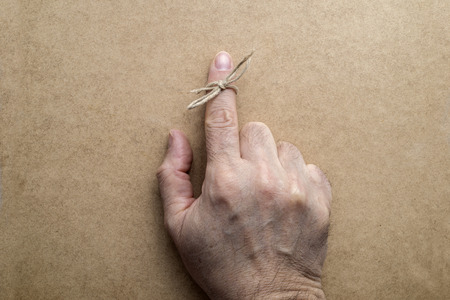 reminding: String on index finger of an elderly man. Wooden background Stock Photo