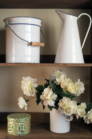 bowl sink: fabric flowers, pitcher and bowl grooming on a wooden shelf Stock Photo
