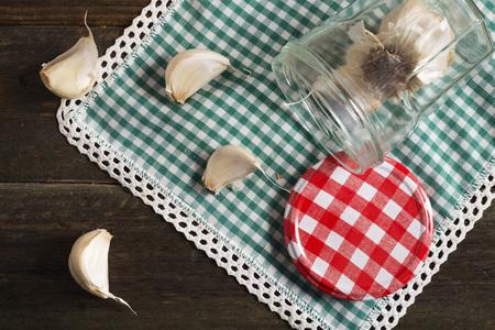glass jar: glass jar with garlic on a checkered tablecloth