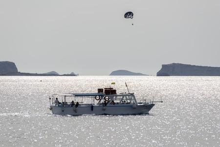 towed: Ibiza. Parasailing - summer kiting activity, person is towed behind a boat