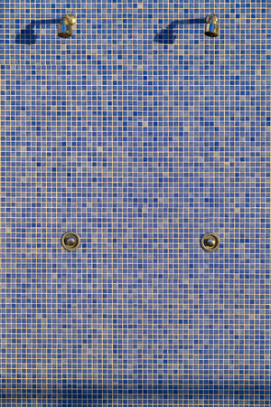 showers: showers and taps on a tiled wall