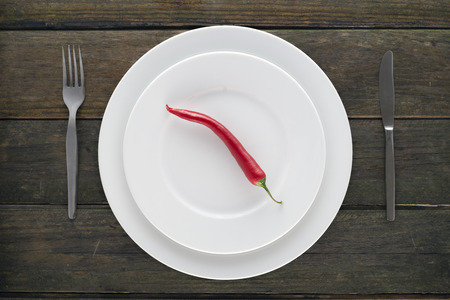 peppery: table service and chilli on an old wooden table