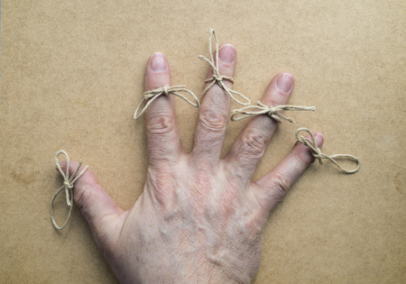 reminding: Twine in the fingers of an elder. Wooden background