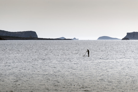 boarders: Silhouettes of Stand up paddle surfers (paddle boarders) at sunset. Ibiza coast Stock Photo