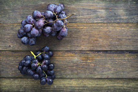 bunches: two bunches of black grapes on an old wooden table. Space for text
