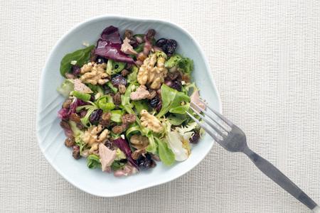 escarola: ensalada con nueces, pasas, foie gras; los ar�ndanos, la granada, escarola, achicoria y lechuga. Sazonado con aceite de oliva, sal y vinagre bals�mico Foto de archivo