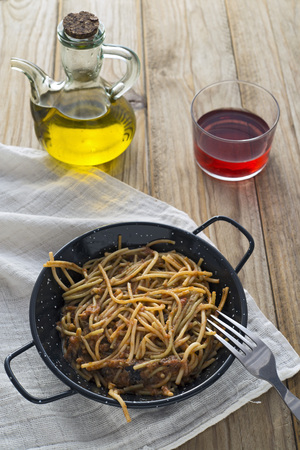 red cooked: Spaghetti with tomato sauce on wooden table. Not forgetting the glass of claret Stock Photo