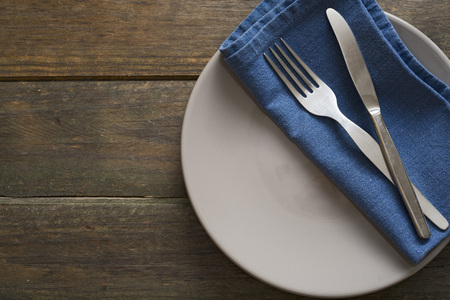 silver cutlery: Silver cutlery and a napkin on dark wooden table