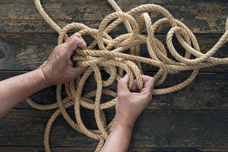 unravel: Two hands trying to untangle a rope. Wooden background Stock Photo