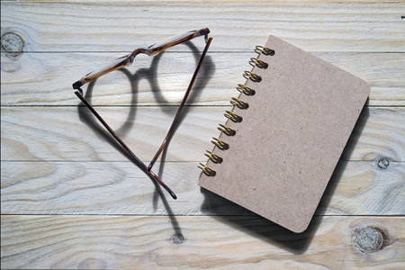 glasses and notebook on wooden background