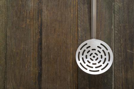 straining: straining spoon on dark wood