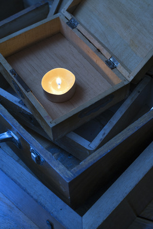 fragile industry: burning candle on a wooden box Stock Photo