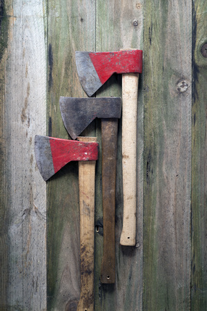 axes: Three axes on a wooden background
