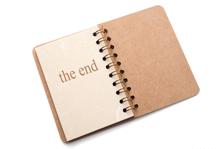 narration: The text the end written on the last page of a notebook. Isolated on white background