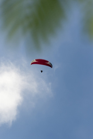 parapente: Paragliding on the Canary Islands. Red paraglider against  blue sky.