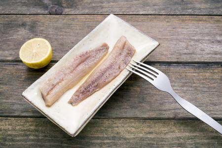 sardinas: plato r�stico de sardinas ahumadas con lim�n Foto de archivo